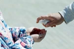 Prevention of Coronavirus Disease COVID-19. Dad splashes on his daughter's arms hand sanitizer.