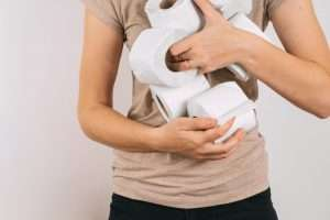 Woman hands with pile of toilet rolls, pandemic panic
