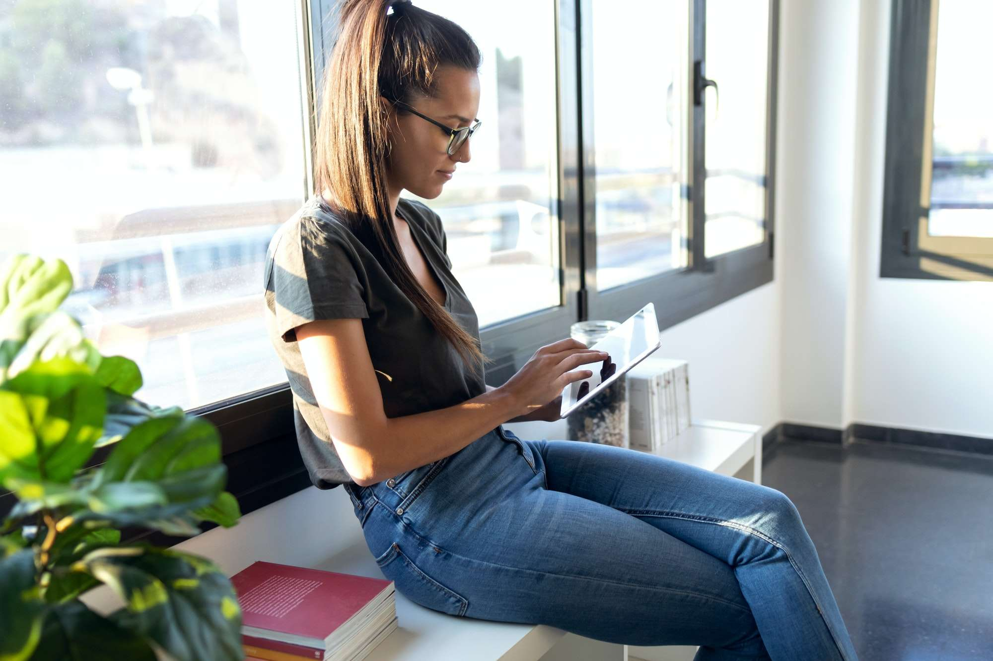 Pretty young business woman using her digital tablet while sitting next to the window in the office.
