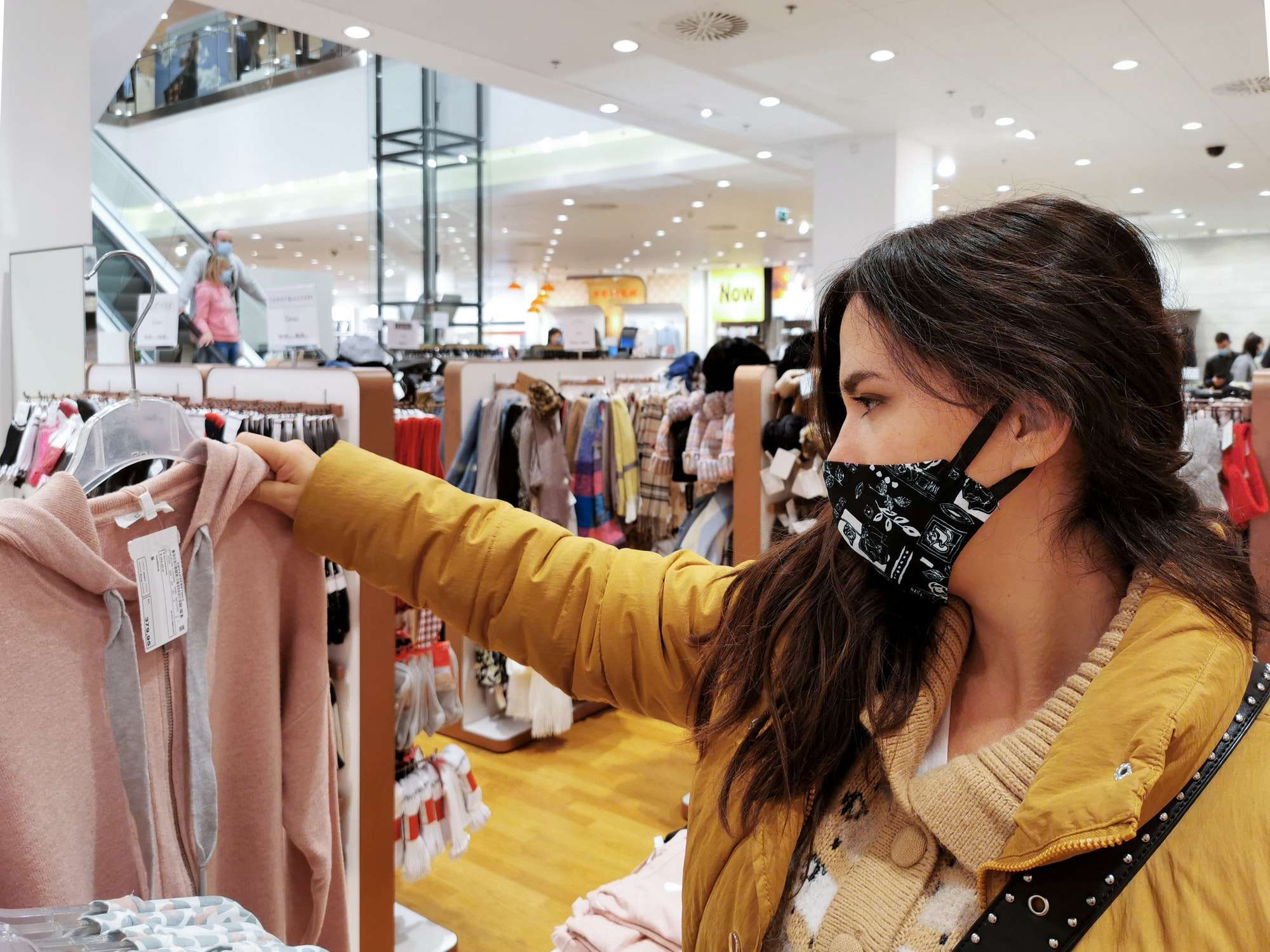 Young woman shopping for clothes. Retail shopping, mask, wearing mask, corona, covid.
