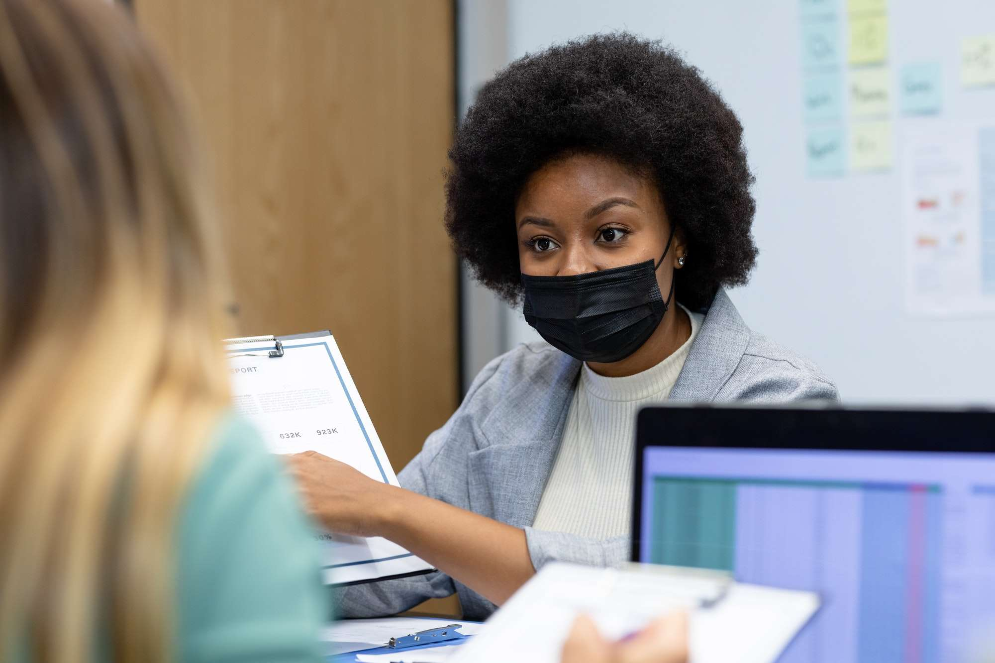 African american businesswoman wearing mask pointing at document