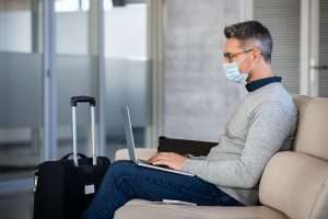 Mature business man wearing mask while commuting and using laptop