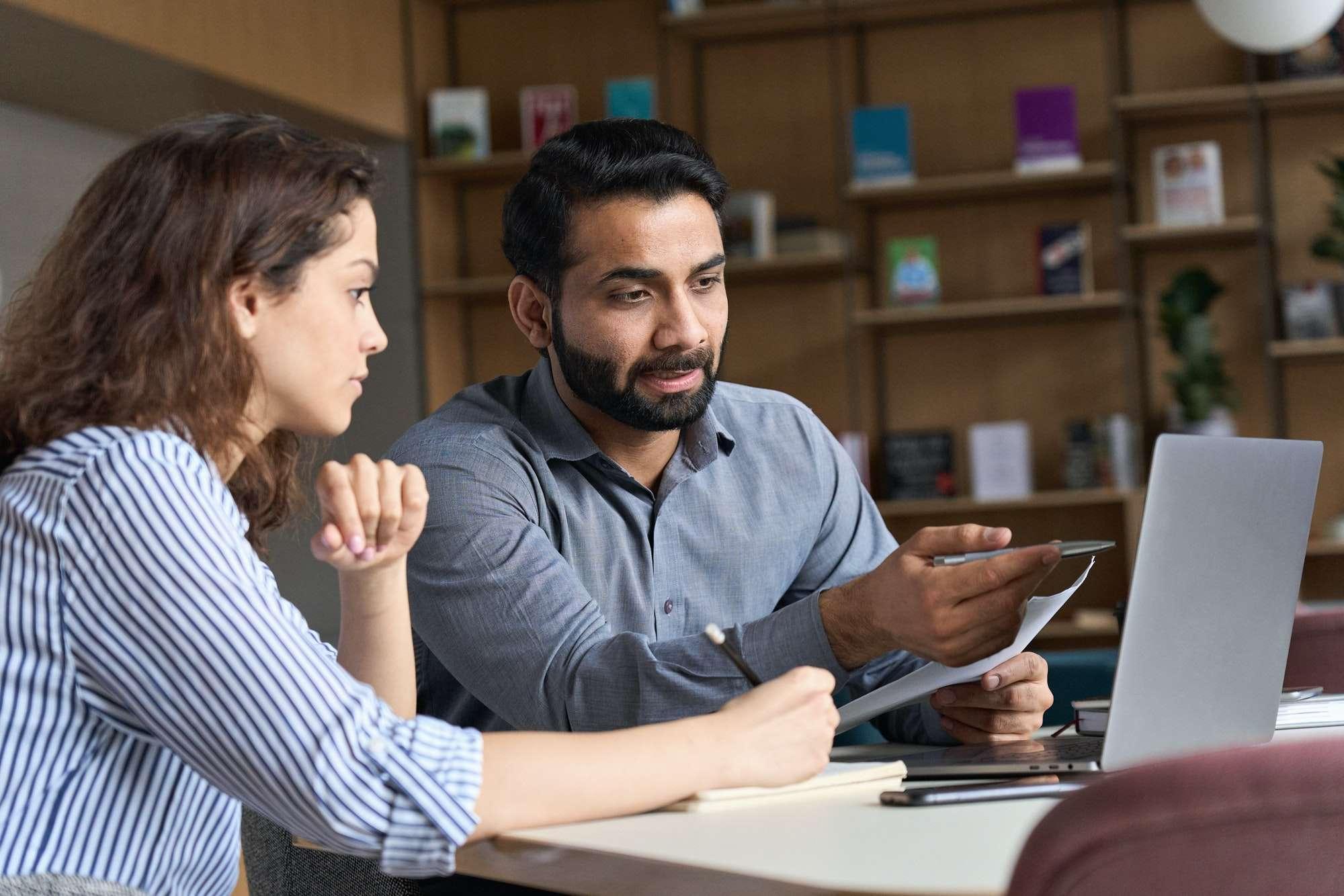 Indian teacher or mentor helping latin student, teaching intern using laptop.